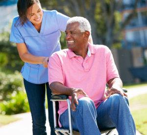 caretaker pushing a senior man in wheelchair